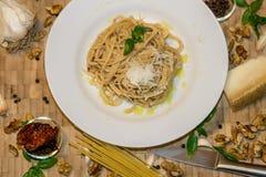 新鲜的面团用红色pesto调味汁、巴马干酪和坚果 免版税库存照片