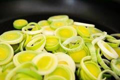 新鲜的韭葱特写镜头在煎锅切了圆的圆环放置 库存图片