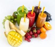 新鲜的颜色汁液圆滑的人绿色黄色红色桔子紫罗兰色白色热带水果 免版税库存图片