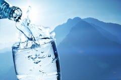 新鲜的饮用水倾吐玻璃以山为背景 免版税图库摄影