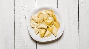 新鲜的馄饨用在板材的乳酪 橄榄凤尾鱼汤 免版税库存照片