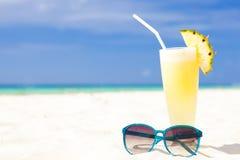 新鲜的香蕉和在热带海滩的菠萝汁和太阳镜的照片 免版税库存图片