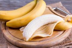 新鲜的香蕉和被剥皮的香蕉在切板 免版税库存图片