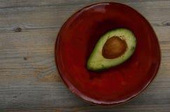 新鲜的鲕梨半在一个红色陶瓷茶碟 免版税库存照片