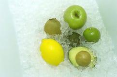 新鲜的鲕梨,猕猴桃,绿色苹果,在冰背景的柠檬 图库摄影