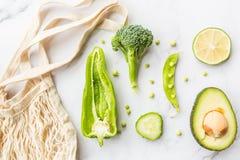 新鲜的鲕梨,石灰,硬花甘蓝,绿豆,黄瓜,青椒 r r 说谎在白色大理石的绿色菜 库存照片