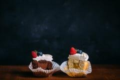 新鲜的鲜美杯形蛋糕用莓果 选择聚焦 背景黑暗木 土气样式,文本的地方 切杯形蛋糕 免版税库存照片