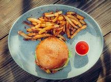 新鲜的鲜美汉堡和炸薯条在木桌上 库存图片