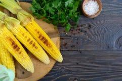 新鲜的鲜美烤甜玉米用黄油、海盐和香菜在一张木桌上 免版税库存图片