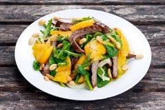 新鲜的鲜美芒果、牛肉沙拉与菜和坚果 图库摄影