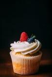 新鲜的鲜美香草杯形蛋糕用莓果 选择聚焦 背景黑暗木 土气样式,文本的地方 免版税库存图片