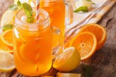 新鲜的鸡尾酒用桔子、柠檬、冰和薄菏在一个玻璃瓶子 免版税图库摄影