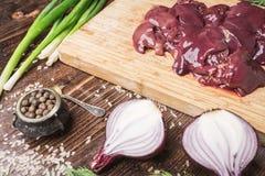 新鲜的鸡肝,红洋葱,黑胡椒,在黑褐色木背景的疏散米 免版税库存照片