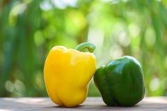 新鲜的黄色和绿色甜椒胡椒木和自然绿色背景 免版税库存图片