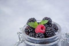 新鲜的黑莓和一个莓特写镜头与一片薄荷的叶子在一个玻璃瓶子在土气桌上 免版税库存照片