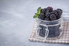 新鲜的黑莓特写镜头与一片薄荷的叶子的在土气桌上的一个玻璃瓶子 免版税库存照片