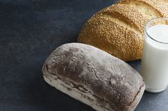 新鲜的黑麦面包和白面包与种子,杯牛奶 国家早餐的概念早晨 免版税图库摄影