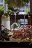 新鲜的龙虾和瓶在桌上的白葡萄酒 库存照片