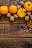 新鲜的水多的成熟蜜桔用叶子核桃和桂香在木头 免版税库存图片