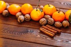 新鲜的水多的成熟蜜桔用叶子核桃和桂香在木头 免版税图库摄影
