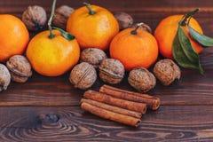 新鲜的水多的成熟蜜桔用叶子核桃和桂香在木 免版税库存图片