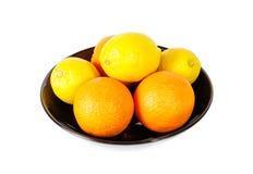 新鲜的水多的桔子和柠檬在白色隔绝的黑碗 免版税库存照片