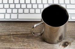 新鲜的黑暗的咖啡与键盘的在土气木桌面上 免版税图库摄影