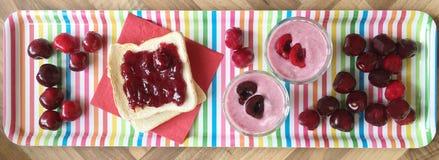 新鲜的水果的早餐多士用樱桃果酱、樱桃酸奶和新鲜的樱桃 顶视图 免版税库存照片