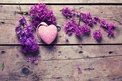 新鲜的紫罗兰色淡紫色花和装饰桃红色心脏在变老 免版税库存照片