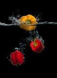 新鲜的黄色和红色辣椒粉飞溅在水中 库存图片