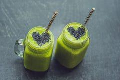 新鲜的绿色圆滑的人用香蕉和菠菜与sesam的心脏 图库摄影