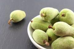 新鲜的绿色杏仁在一个小白色碗结果实 免版税库存照片