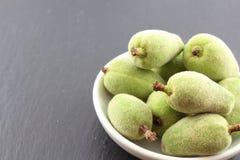 新鲜的绿色杏仁在一个小白色碗结果实 免版税库存图片