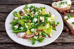 新鲜的绿色芦笋沙拉巫婆山羊乳干酪、豌豆、radishe、夏南瓜、莴苣和榛子 免版税图库摄影