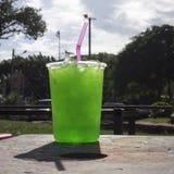 新鲜的绿色苏打在与桃红色管的一块大塑料玻璃冰了在有玻璃,天光,阳光的阴影的公园 库存图片
