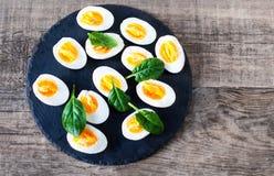 新鲜的绿色菠菜婴孩叶子和煮沸的鸡蛋在一半切开了  免版税库存图片