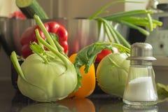 新鲜的绿色kohlrabis,红色和黄色辣椒粉,盐瓶 库存照片