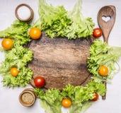 新鲜的莴苣、西红柿、香料和一把木匙子沙拉的,在切板正文附近在木土气后面 库存照片