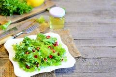 新鲜的莴苣用石榴穿戴了用柠檬汁和橄榄油 明亮的容易的素食食物 在板材的健康沙拉 图库摄影