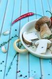 新鲜的porcini蘑菇和草本在煎锅在木桌上 库存照片