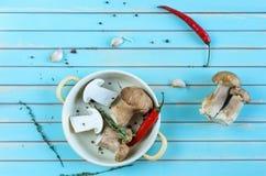 新鲜的porcini蘑菇和草本在煎锅在木桌上 免版税图库摄影