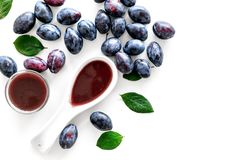 新鲜的tkemali调味汁 传统白种人,英王乔治一世至三世时期调味汁或李子果酱在匙子在李子附近在白色背景顶视图 库存照片