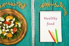 新鲜蔬菜、卷尺和笔记薄沙拉与文本& x22; 健康食物! & x22; 免版税库存图片