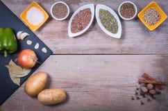 新鲜蔬菜、香料和草本在碗 烹调的自然和生物成份在木背景 免版税图库摄影