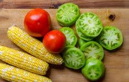 新鲜蔬菜包括玉米、蕃茄和切的绿色蕃茄 免版税库存照片