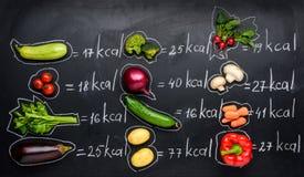 新鲜蔬菜和卡路里在黑色隔绝的桌 库存照片