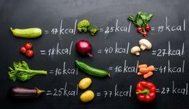 新鲜蔬菜和卡路里在黑色隔绝的桌 免版税库存照片