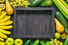 新鲜蔬菜和果子背景与一个空的木盘子 黄色和绿色菜框架  一张顶视图,一个地方为 免版税库存图片