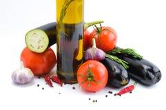 新鲜蔬菜和被隔绝的橄榄油瓶  免版税库存图片