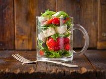 新鲜蔬菜在玻璃瓶子的草莓沙拉在自然土气 图库摄影